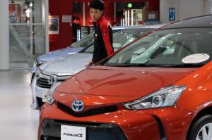 A Toyota Motor Corp. employee checks vehicles at the company's showroom in Tokyo. Toyota and Mazda Motor Corp. are considering sharing fuel-efficient technologies.  Photo:  Yoshikazu Tsuno/Agence France-Presse/Getty Images
