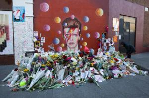 Floral tributes are placed in front of a mural of Bowie in Brixton, south London. (JUSTIN TALLIS/AFP/Getty Images)